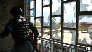 A member of the Afghan security forces searches a damaged  Kabul building, 16 April