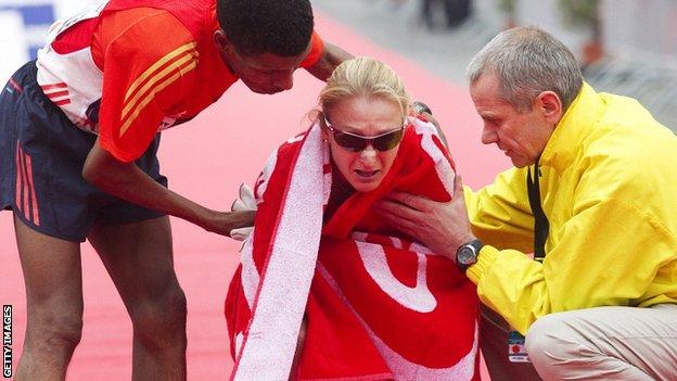 Haile Gebrselassie (L) and chief organiser Wolfgang Konrad (R) help Paula Radcliffe