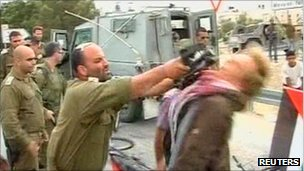 A still from video footage showing the demonstrator being hit in the face with a gun