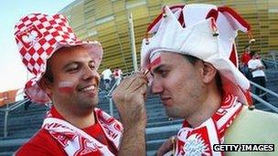 Polish football fan painting second fan's face
