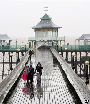 Holidaymakers walking on a pier in the rain (Image: AP)