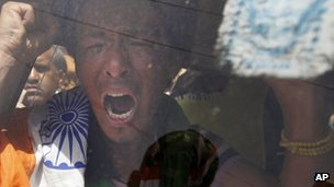 A Tibetan exile shouts slogans as he is detained by Indian police during a protest against the visit of Chinese President Hu Jintao
