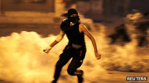 An anti-government protester runs holding a teargas canister fired by riot police during clashes after a procession to visit the grave of Ismael Abdulsamad in the village of Salmabad south of Manama, April 16, 2012.