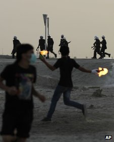 Bahraini anti-government protesters throw petrol bombs at riot police firing tear gas during clashes Monday, April 16, 2012, in Salmabad, Bahrain