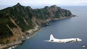 A Japan Maritime Self-Defence Force&#039;s P-3C Orion surveillance plane flies over the disputed Senkaku / Diaoyu islands in the East China Sea, 13 October 2011