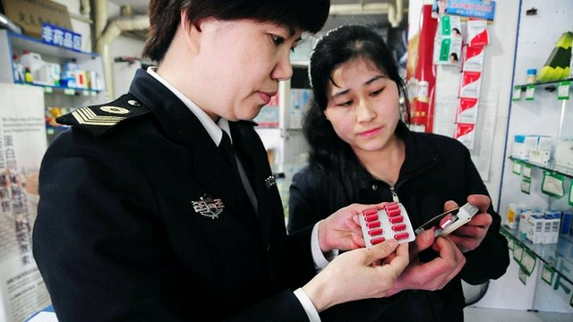 A Chinese official investigating medicine in a chemists in Qingdao, China