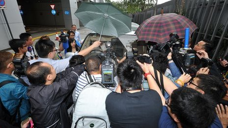 Reporters and photographers crowd a vehicle carrying Chairman of Sun Hung Kai Properties Thomas Kwok