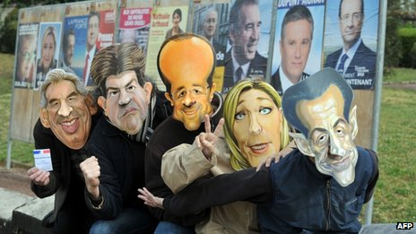 Employees of the Cesar mask-making company pose in front of electoral billboards wearing 2012 French presidential election candidates&#039; masks in Saumur, western France, 18 April