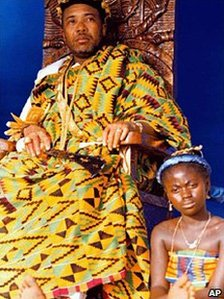 Liberian President Charles Taylor sits on a throne with a traditional dancer sitting at his feet during a ceremony in Monrovia where Ghanaian immigrants crowned him Chief Okatakyie The Greatest of Warriors - February 1998