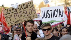 Spaniards hold placards calling for justice during a general strike