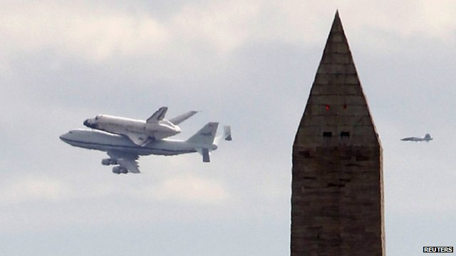 Space shuttle Discovery piggy-back on a 747, flying past the Washington Monument