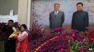 Families posing in front of the picture of Kim Il Sung and Kim Jong Il
