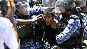 Riot policemen detain a supporter of former President Mohamed Nasheed during a protest near the parliament against President Mohammed Waheed Hassan, 19 March 2012