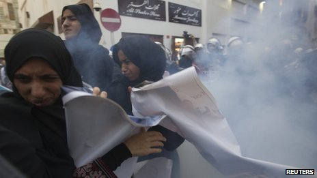 "Women protesters run after a stun grenade is fired at them in Old Manama (18 April 201"")"