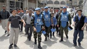 "A handout photograph released by Syria's national news agency SANA, shows Moroccan Colonel Ahmet Himmiche (3rd L), leader of the first UN. monitoring team in Syria, during a visit with his team to one of Damascus"" suburbs"