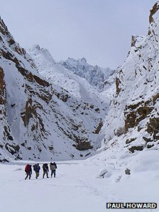 Four people walking through the Zanskar river gorge