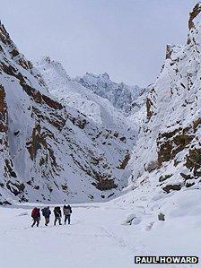 Four people walking through the Zanskar river gorge