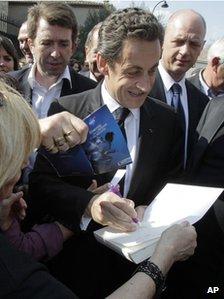 Nicolas Sarkozy signing a book
