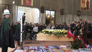 Mourners standing by the coffin inside the church