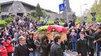 Picture of the coffin being carried down the steps in front of the church with a large crowd of people behind it.