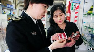 An official from local Food and Drug Administration, left, checks out capsule medicine in a drug store in Qingdao in east China's Shandong province, 16 April 2012