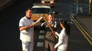 Volunteers touch torches to simulate passing the Olympic Flame