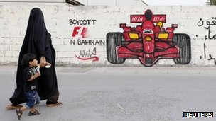 A woman and boy walk past graffiti urging the boycott of the 2012 Bahrain Grand Prix (18 April 2012)