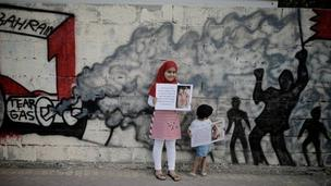 Bahraini children hold up pictures of activists allegedly tortured by security forces in Bahrain, behind graffiti demanding the cancelling of Sunday's Grand Prix (19 April 2011)