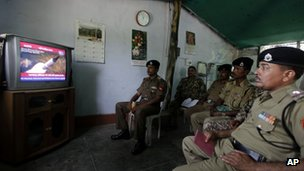 Indian Border Security Force officers watch television coverage of the launch of India's Agni-V missile