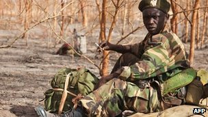 Photo taken on 15 April 2012 of a South Sudanese soldier waiting amongst acacia trees at the front line just north of Heglig