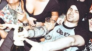 An image posted by Hunter Moore (on right, pointing, with hat) at a party