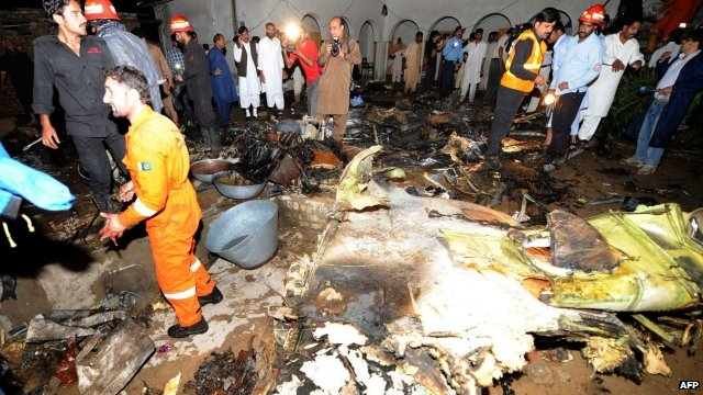 Pakistani rescue workers search the site of the plane crash