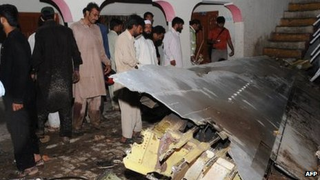 Pakistani villagers look at the plane&#039;s wreckage