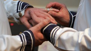 A man putting a wedding ring on another man&#039;s hand
