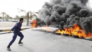 A riot policeman tries to put out fire from tyres set aflame by anti-government protesters in Budaiya