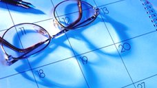 Eyeglasses and fountain pen on top of a calendar