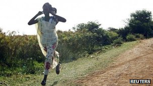 A woman runs along a road during an air strike in Rubkona near Bentiu April 23, 2012.
