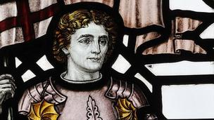 A stained glass window depicting Saint George. He is a fair, pleasant faced gentleman carrying the St George's flag.