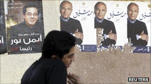 A young man walks past ripped campaign posters for Ahmed Shafiq in Cairo (right)