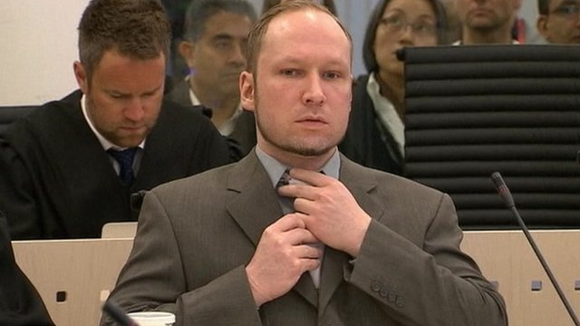 Anders Breivik straightens his tie as he sits in court