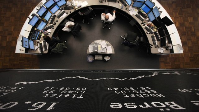 Stock brokers work at the stock exchange in the central German city of Frankfurt.