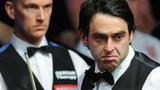 Ronnie O'Sullivan contemplates a shot as Peter Ebdon looks on