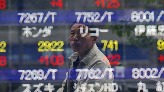 Man looking at a electronic share prices in Tokyo, April 18, 2012