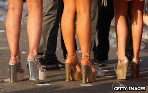 Ladies Day racegoers in platform heels at Aintree Grand National meeting