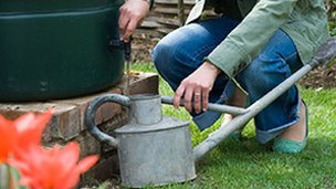 Gardner filling watering can from a water butt