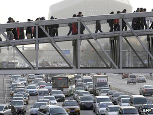 Pedestrians walk on a sky bridge in downtown Beijing (file photo)
