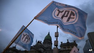 "Supporters of an oil nationalization bill proposed by Argentina's President Cristina Fernandez holds up flags reading in Spanish ""Fight and return YPF"" outside Congress"