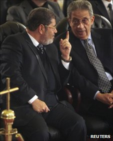 Mohammed Mursi and Amr Moussa talk together at St Mark&#039;s Cathedral in Cairo on 6 January