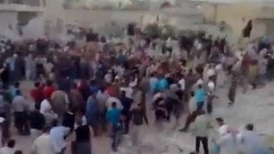 Crowds gather and pull bodies from the rubble following a blast in Hama