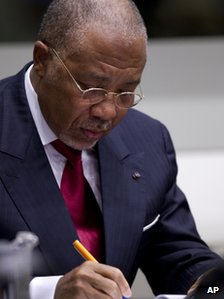 Former Liberian President Charles Taylor takes notes as he waits for the start of a hearing to deliver verdict in the court room of the Special Court for Sierra Leone in Leidschendam